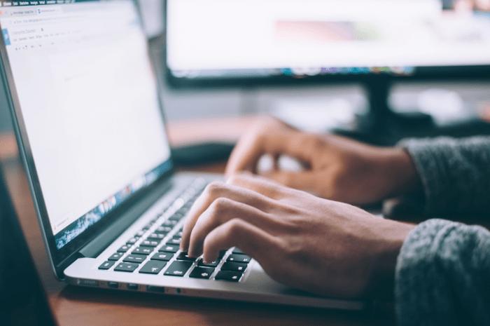 Ein Mann nutzt die Tastatur eines Laptops, nur die Hände und der Laptop sind zu sehen.