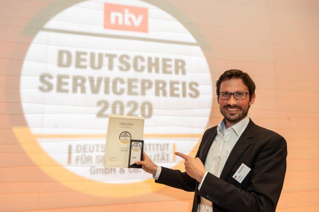 Jan Rabe, Gründer von Wechselpilot, posiert beim Deutschen Servicepreis 2020 mit der Urkunde für ausgezeichneten Service.