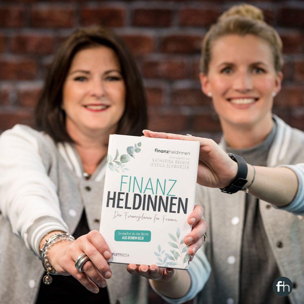 """Jessica Schwarzer und Katharina Bremer halten gemeinsam ihr Buch """"Finanz-Heldinnen: Der Finanz-Planer für Frauen"""" in die Kamera."""