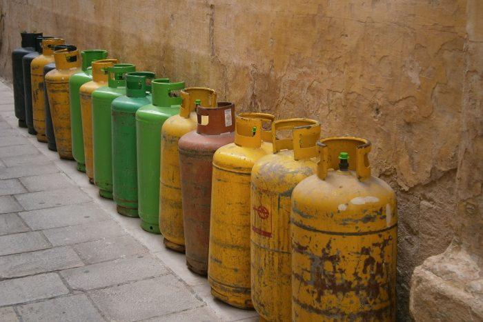 Mehrere Gasflaschen stehen nebeneinander vor einer Wand.