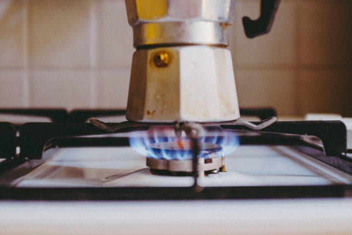 Ein Espressokocher steht auf einem Gasherd.