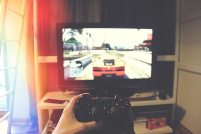 Hand mit Spielekonsole vor Fernseher