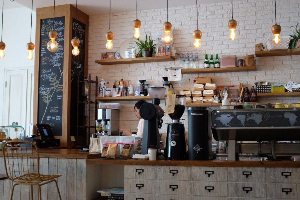 In einem Café arbeitet ein Mitarbeiter hinter dem Tresen.