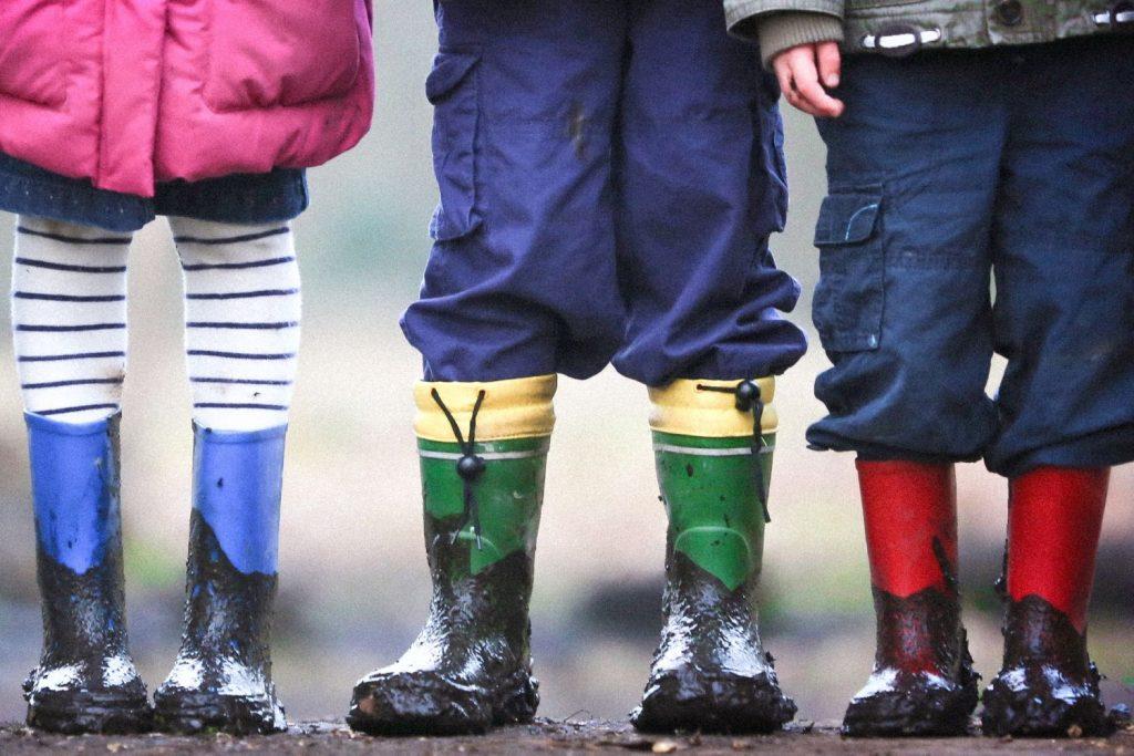 Drei Kinder stehen in dreckigen Gummistiefeln draußen nebeneinander, nur ihre Beine sind zu sehen.