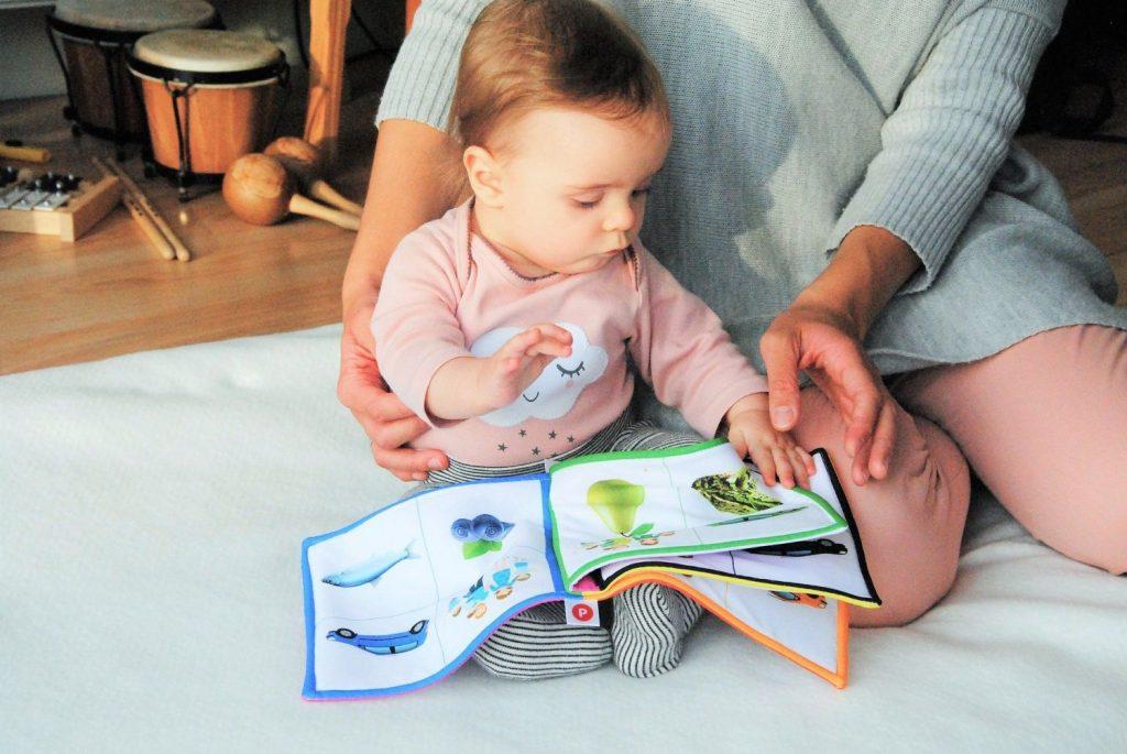 Ein Kleinkind sitzt auf einer Decke und liest mit seiner Mutter ein Buch.