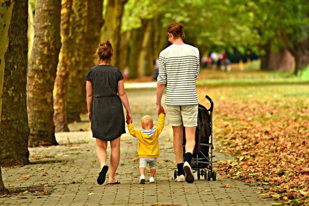 Eine Mutter und ein Vater gehen mit ihrem Kleinkind in der Mitte in einem Park spazieren.