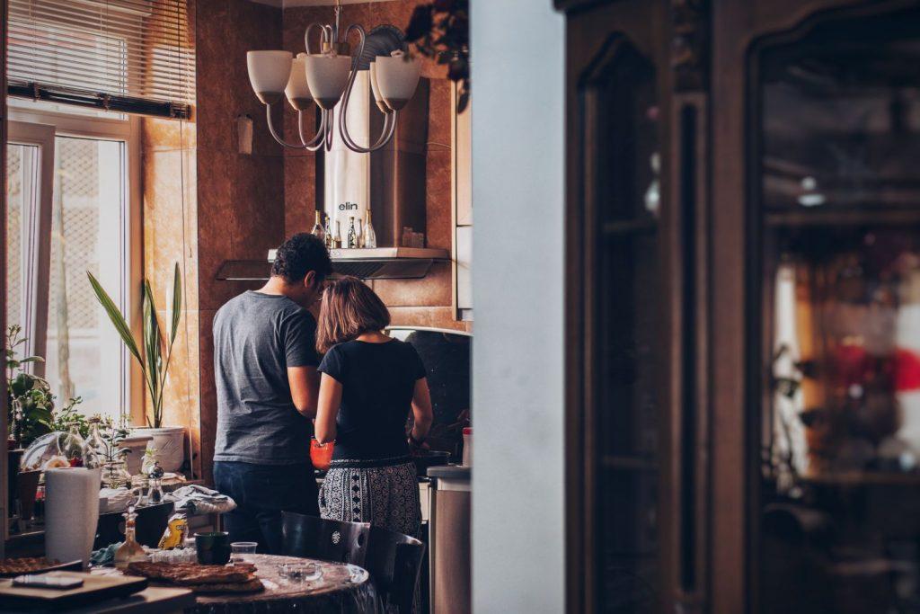 Ein Mann und eine Frau stehen gemeinsam am Morgen in der Küche und machen sich einen Kaffee.
