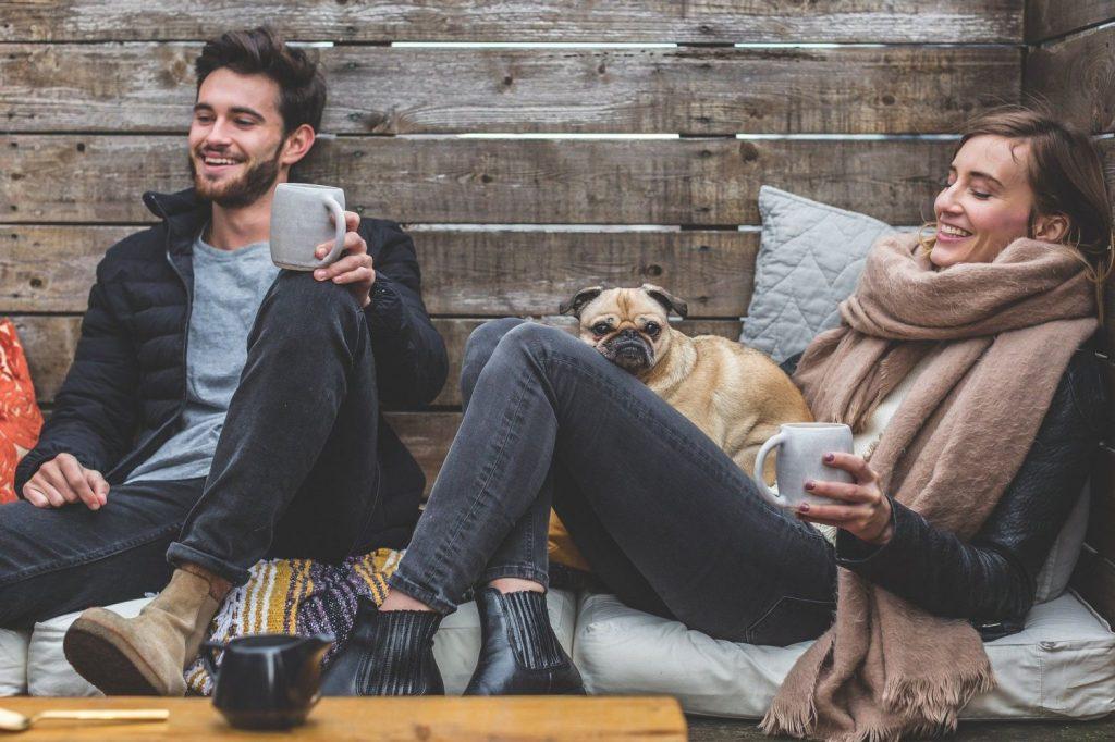 Ein Mann und eine Frau sitzen gemütlich in einer Sitzecke draußen mit einem Hund.