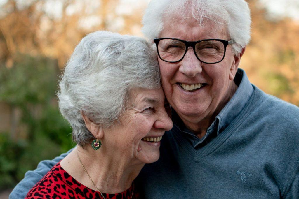 Ein Paar im Rentenalter posiert eng umschlungen und lachend für ein Foto.