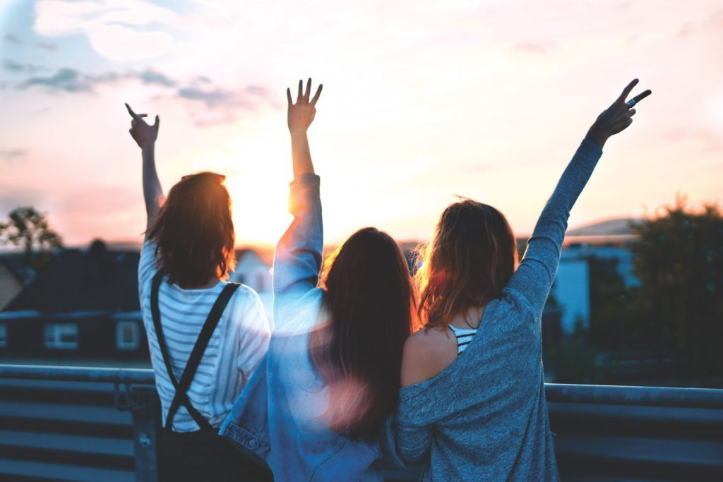 Drei junge Frauen stehen zusammen auf einem Dach, schauen in den Sonnenuntergang und strecken ihre Arme in den Himmel.