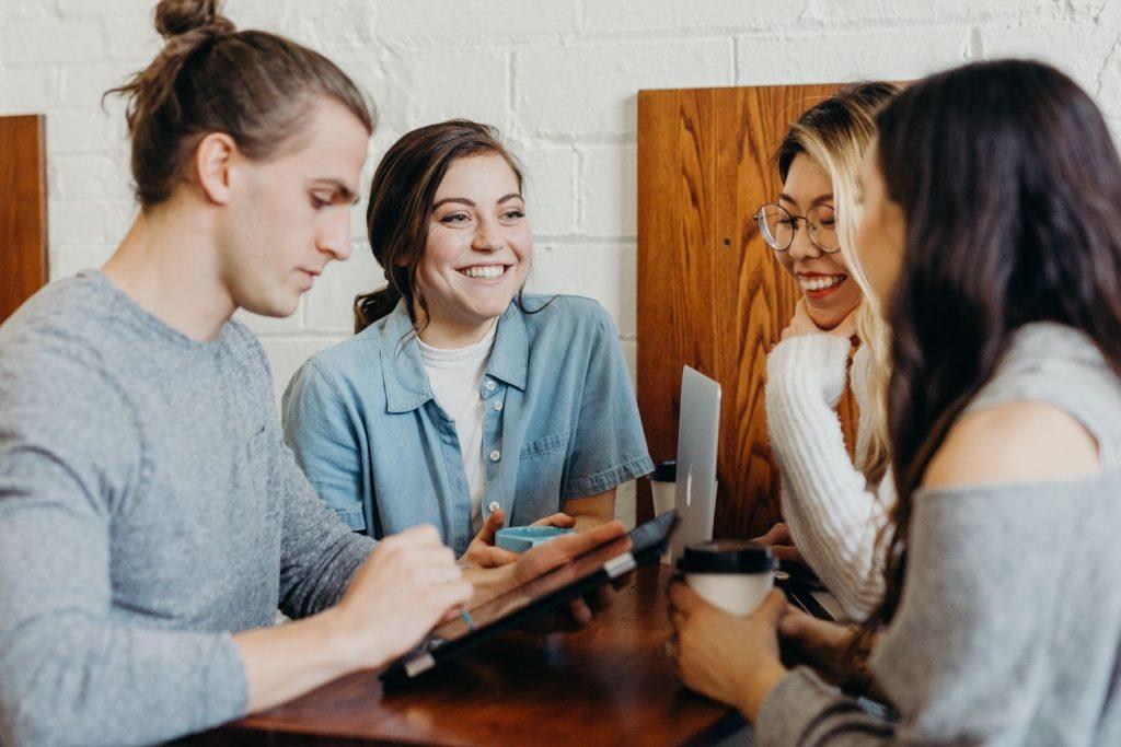 Vier junge Menschen sitzen gemeinsam an einem Tisch und unterhalten sich.