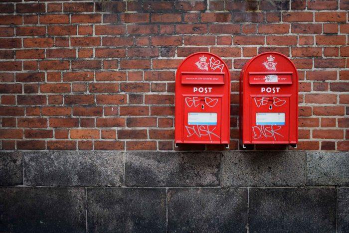 Zwei rote Briefkästen nebeneinander an einer Steinwand